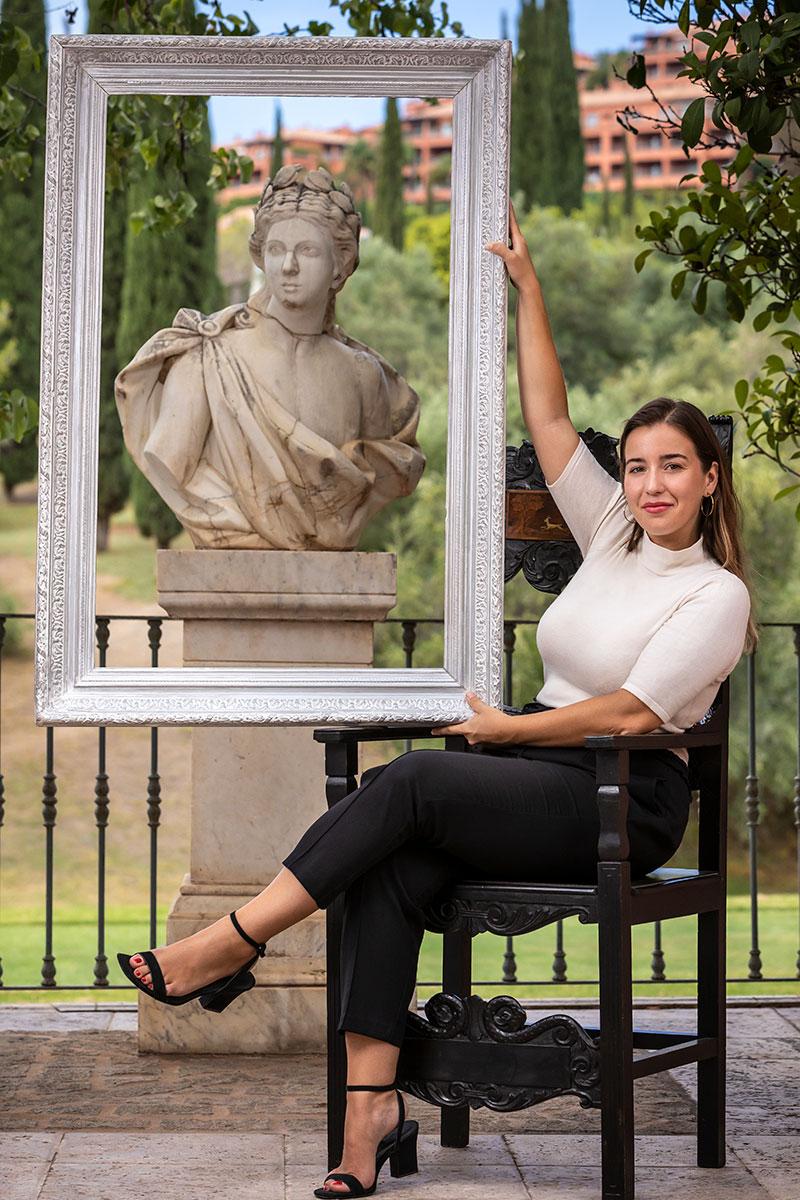 galerista enmarcando una estátua