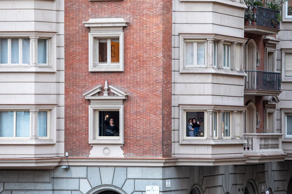 tres personas en sus ventanas con su móvil