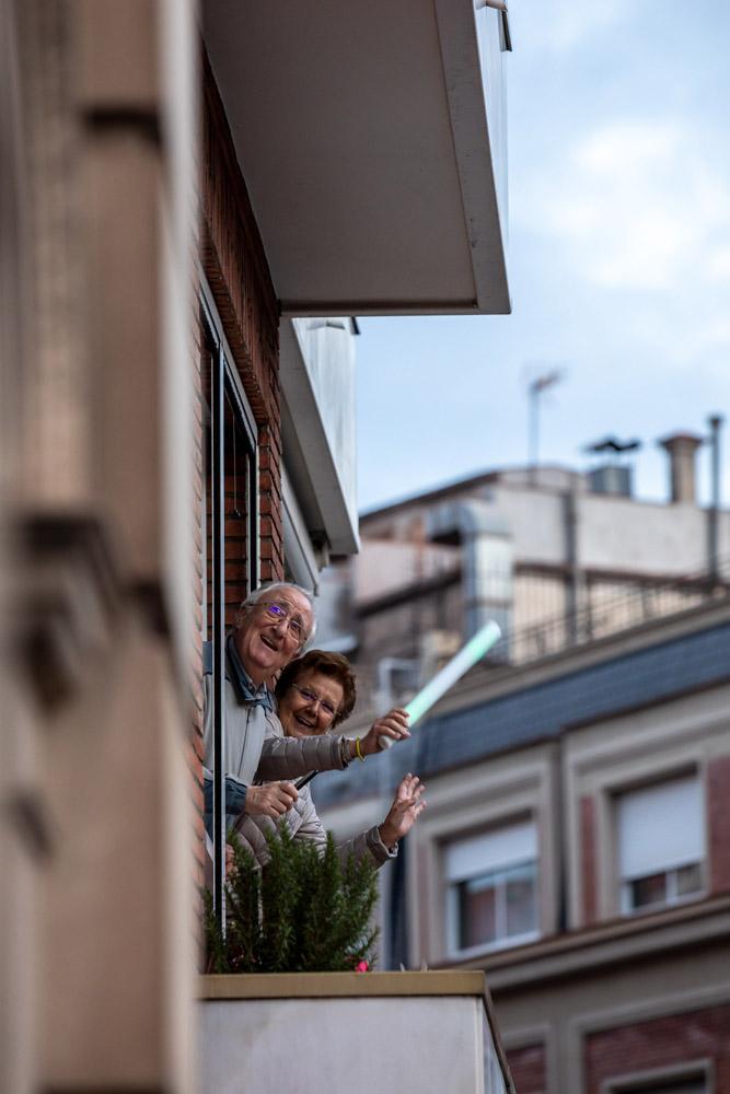 dos personas mayores a su balcón sonriendo