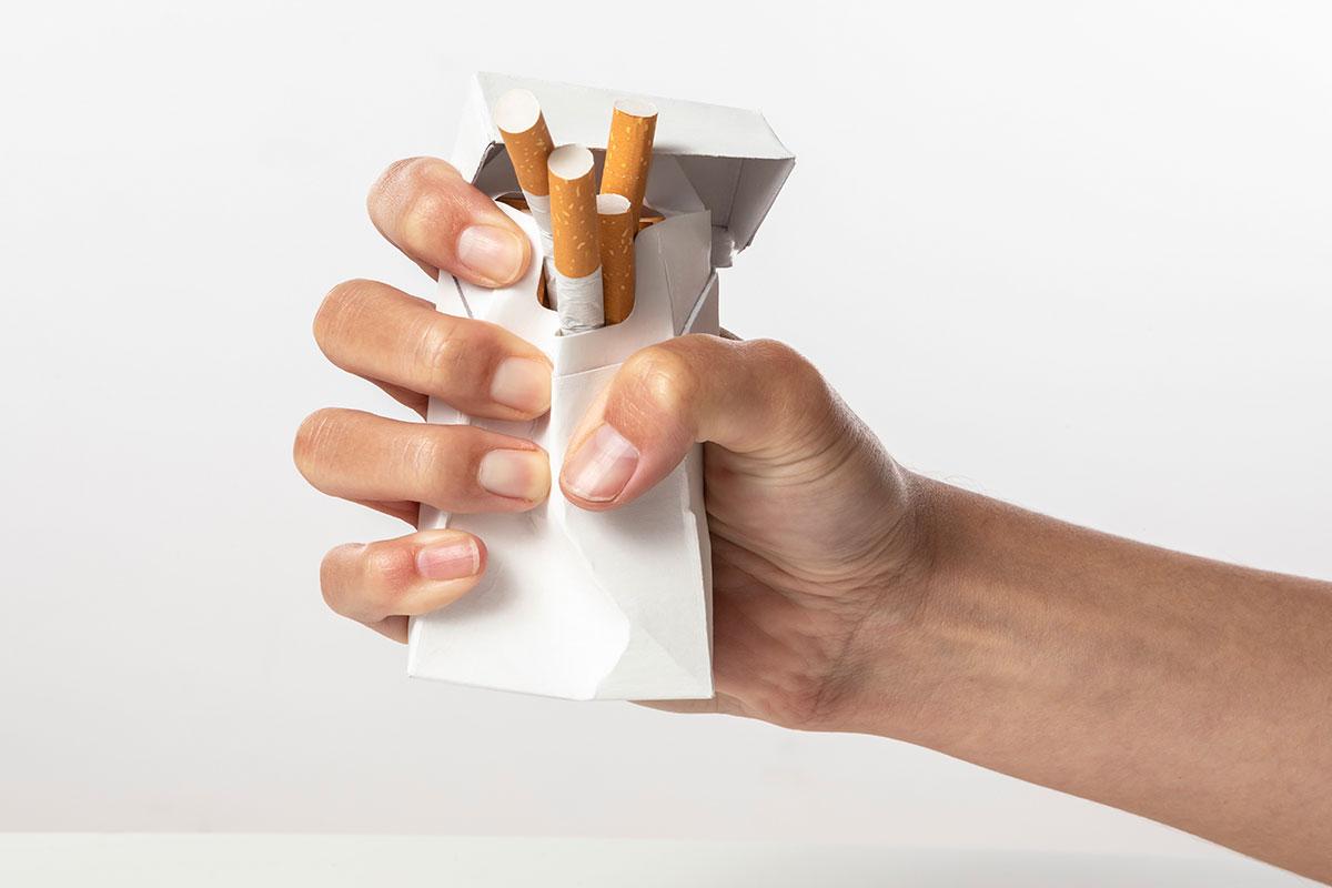 paquete de tabaco con mano que lo rompe